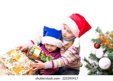 Cute little girls in Santa's hat near Christmas tree.