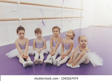 Cute little girls sitting on the floor, resting after ballet lesson at dance studio. Adorable little ballerinas wearing tutus relaxing together after exercising. Health, lifestyle, innocence concept