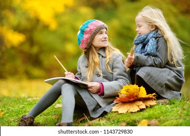 Cute little girls sketching outside on beautiful autumn day. Happy children playing in autumn park. Kids drawing with colourful pencils. Autumn activities for children.