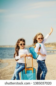 Cute little girls with suitecases on the beach are ready to travel. Summertime concept.
