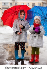 cute little girls walking through   puddles in   early spring.