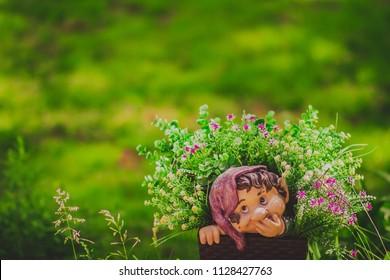 Cute little gnome garden model, summer decorative statue, outdoor sculpture, fantasy figure in grass