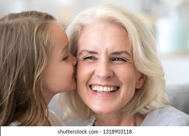 Cute little grandchild kissing excited grandmother on cheek, laughing grandma enjoying care of grandchild congratulate with mothers day, showing support and love, warm family relations close up