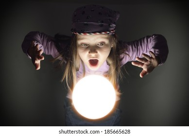 Cute little gypsy girl amazed over a glowing crystal ball, seeing the future