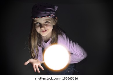 Cute little gypsy girl with a glowing crystal ball, offering to predict the future