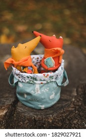 Im Herbstgarten sitzen kleine, handgemachte Spielzeuge in einem Korb. Kindheit, Baby, Urlaub, Menschen, Hobby, Emotionen Konzepte.