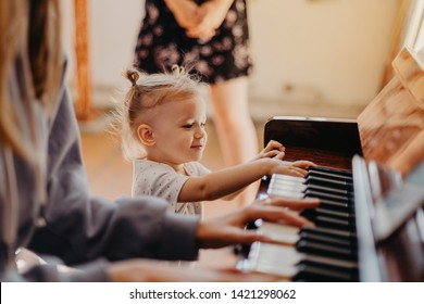 Cute little happy child girl playing piano in a light room. Selective focus, noise effect