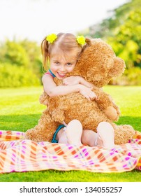 Cute little happy girl hugging big brown teddy bear and sitting down on green grass meadow, spring season