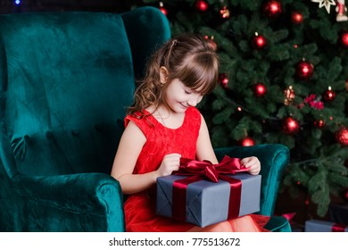 Cute little happy girl with present box sitting in chair near Christmas tree. Horizontal color photography.