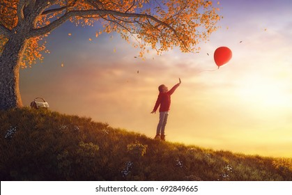 Cute little happy girl walking in autumn Park. Pretty child enjoys the beautiful autumn nature. Kid playing with air balloon.