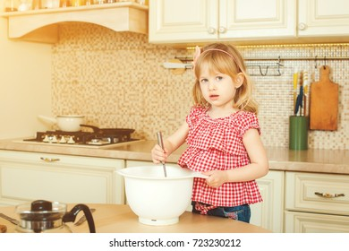 Cute little helper girl helping her mother cooking in the kitchen. Happy loving family are preparing bakery.