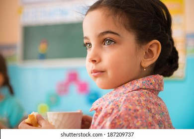 Cute little hispanic girl with cup of milk at daycare