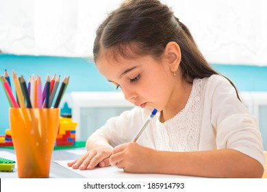 Cute little hispanic girl writing at school