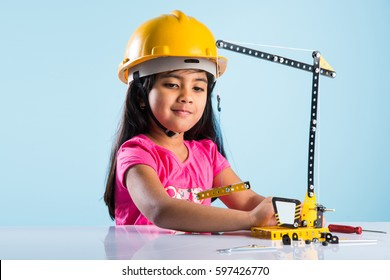 cute little indian baby girl playing with toy crane wearing yellow construction or hard hat, childhood and education concept