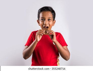 Cute little indian boy eating chocolate, isolated on white background,