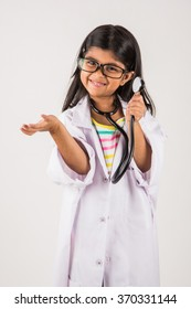 Cute Little Indian girl doctor with stethoscope while wearing Doctor's uniform. Standing isolated over white background