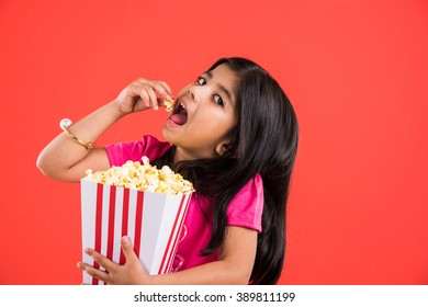 Cute little Indian girl eating popcorn while wearing sunglass or 3D glasses in a theatre. Standing isolated over colourful background