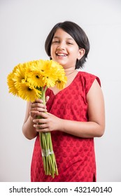 Cute Little Indian Girl holding a bunch / bouquet of Fresh Yellow Gerbera flowers. Isolated over white background