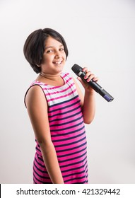 Cute little Indian girl singing in microphone, Standing isolated over white background