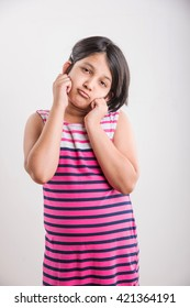 Cute little Indian girl in sorry pose, holding both ears. Standing isolated over white background