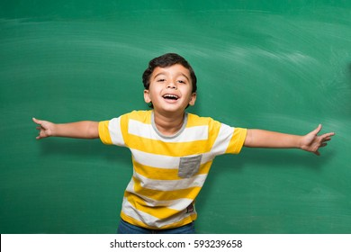 Cute little Indian school kid/boy in hand stretched pose over green chalkboard or chalk board background, isolated