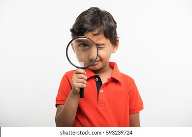 Cute little Indian school kid/boy holding and looking through magnifying glass showing a big eye, isolated over white background