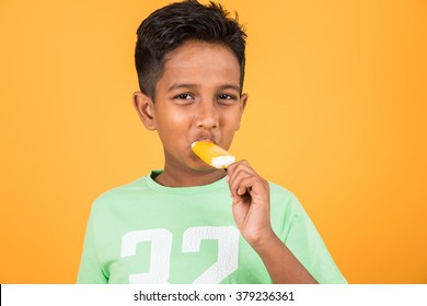 Cute little Indian/Asian boy eating Ice cream/mango bar or candy. Isolated over colourful background