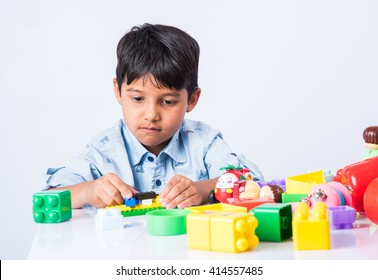 Cute little Indian/asian boy or kid playing with toys / colourful blocks and having fun while sitting at table or isolated over white background
