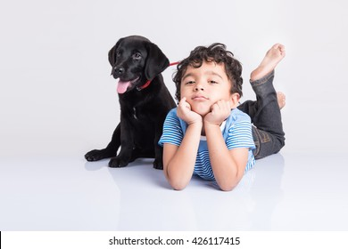 Cute little Indian/Asian boy playing with Black Labrador Retriever puppy while lying or sitting isolated on white background