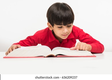 Cute little Indian/Asian boy reading book over study table, isolated over white background