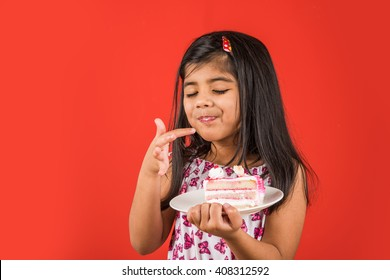 Cute little Indian/Asian girl child eating piece of Strawberry or Chocolate flavoured pastry/cake in a plate. Isolated over colourful background