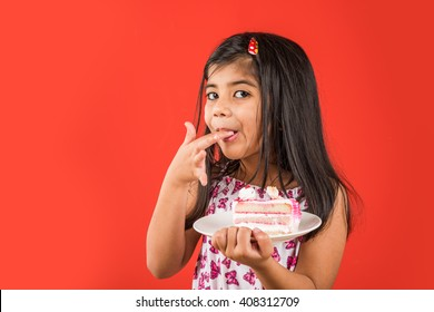 Cute little Indian/Asian girl child eating piece of Strawberry or Chocolate flavoured pastry/cake in a plate or licking fingers. Isolated over colourful background