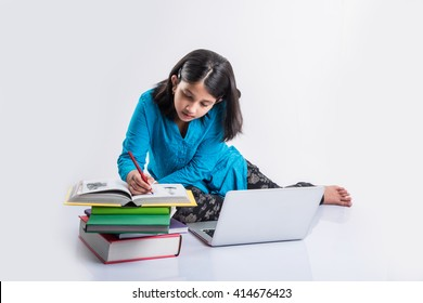 Cute little Indian/Asian girl child studying on laptop or working on school project while lying/sitting on the floor, isolated over white background