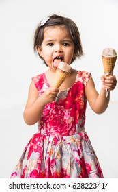 Cute little indian/asian girl child licking or eating chocolate ice cream in cone, isolated over white background