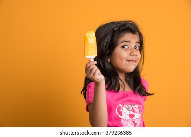 Cute little Indian/Asian girl eating Ice cream/mango bar or candy. Isolated over colourful background