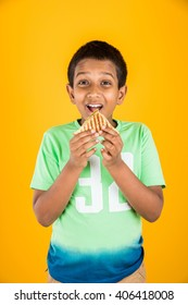 Cute little Indian/Asian girl eating tasty Burger, Sandwich or Pizza in a plate or box. Standing isolated over blue or yellow background.