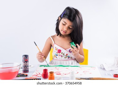 Cute little Indian/Asian Girl enjoying Painting at home with paper, water colour and art brush. Selective focus