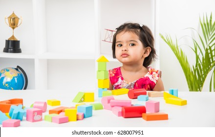 Cute little Indian/asian girl enjoying while playing with toys or blocks, sitting at table