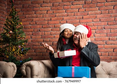 Cute little Indian/Asian Girl and grandfather celebrating Christmas while sitting over sofa with gifts and Xmas Tree at home