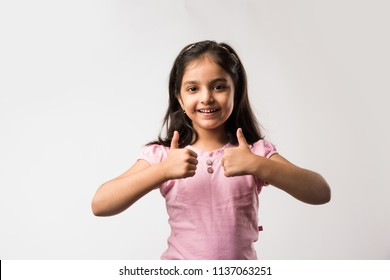 cute little indian/asian girl showing Thumbs up sign, standing isolated over white background
