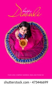 Cute little indian/asian girl in traditional wear holding a diya or Terracotta oil lamp on Diwali festival. top view over pink background
