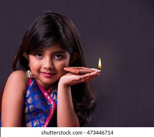 Cute little indian/asian girl in traditional wear holding a diya or Terracotta oil lamp on Diwali festival. front view over black background