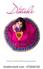 Cute little indian/asian girl in traditional wear holding a diya or Terracotta oil lamp on Diwali festival. top view over white background