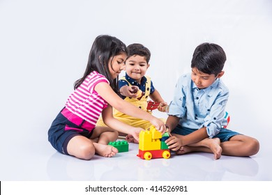 Cute little Indian/asian kids playing with toys or blocks and having fun while sitting at table or isolated over white background