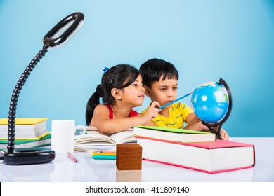 Cute little Indian/Asian kids studying on study table with pile of books, educational globe, isolated over light blue colour