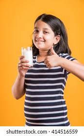 Cute little Indian/Asian playful girl holding or drinking a glass full of Milk, isolated over colourful background