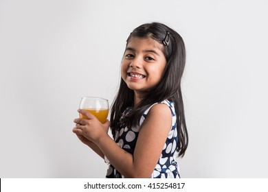 Cute little Indian/Asian playful girl drinking fresh mango/orange juice / cold drink in a glass, isolated over  white background