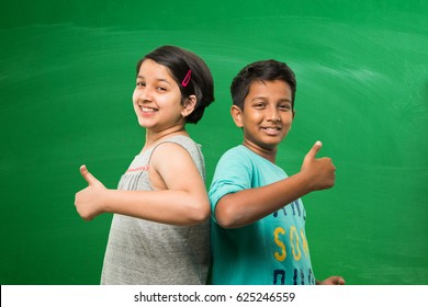 cute little indian/asian  school kids standing in front of empty green chalkboard background showing success or victory symbol with thumbs up