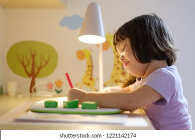 Cute little Japanese girl drawing at her desk in her decorated bedroom.