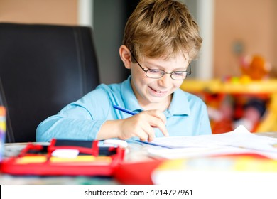 Cute little kid boy with glasses at home making homework, writing letters and doing maths with colorful pens. Little child doing exercise, indoors. Elementary school and education, imagine fantasy